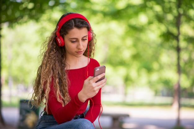 Adolescente vestido de vermelho ouvindo música em um telefone em um parque