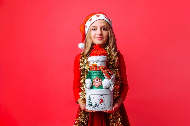 Adolescente, vestindo chapéu de papai noel e enfeites no pescoço, segurando caixas de presente de natal