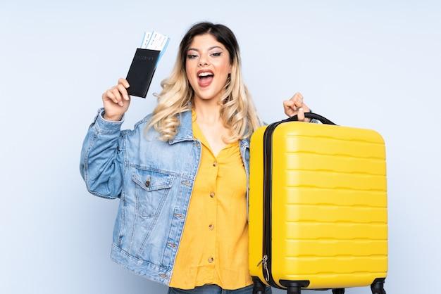 Adolescente viajante segurando uma mala isolada na parede azul em férias com mala e passaporte e surpreso