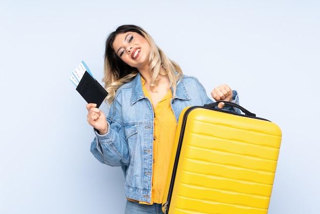 Adolescente viajante segurando uma mala isolada na parede azul em férias com mala e passaporte
