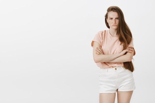 Adolescente zangada e melancólica posando contra a parede branca