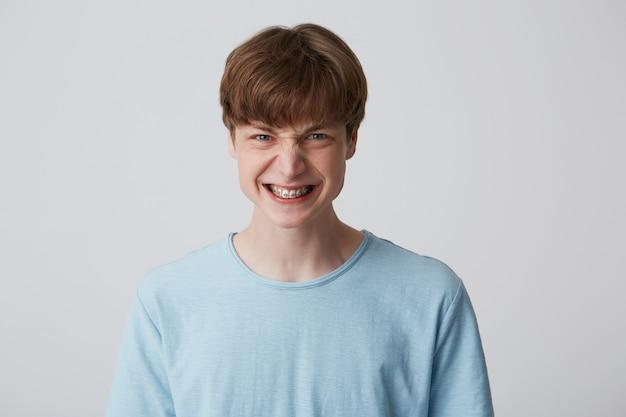 Adolescente zangado, chateado e irado mostra os dentes mostrando o aparelho