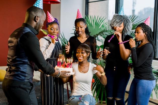 Adolescentes africanos com chifres de festa e um bolo comemorando um aniversário