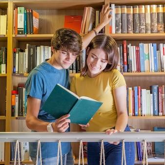 Adolescentes alegres lendo livro na biblioteca