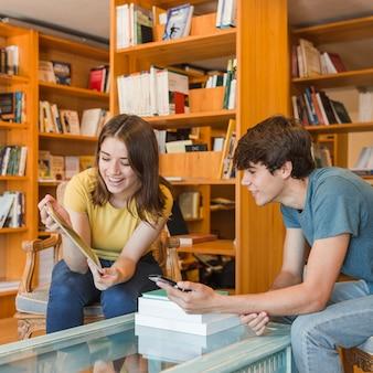 Adolescentes alegres olhando tablet na biblioteca