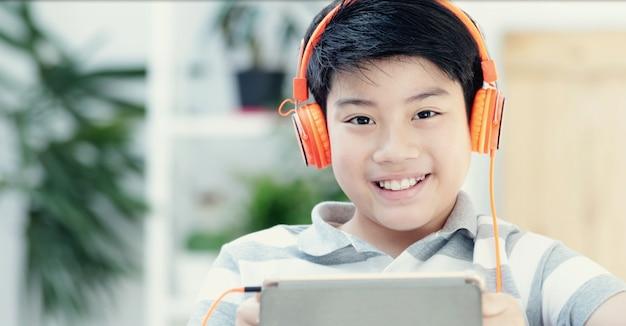 Adolescentes asiáticos que jogam o tablet pc com cara do sorriso.