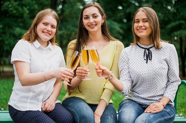 Adolescentes com taças de champanhe, olhando para a câmera
