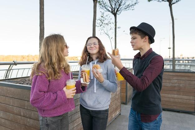 Adolescentes comem comida de rua, amigos, menino e duas meninas, na rua da cidade com hambúrgueres