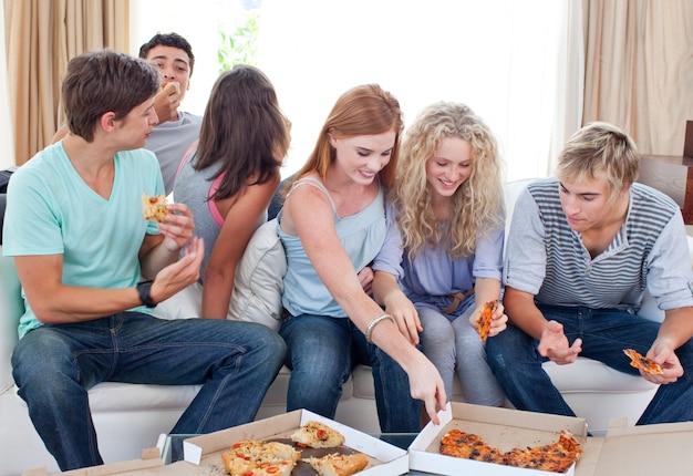 Adolescentes comendo pizza em casa