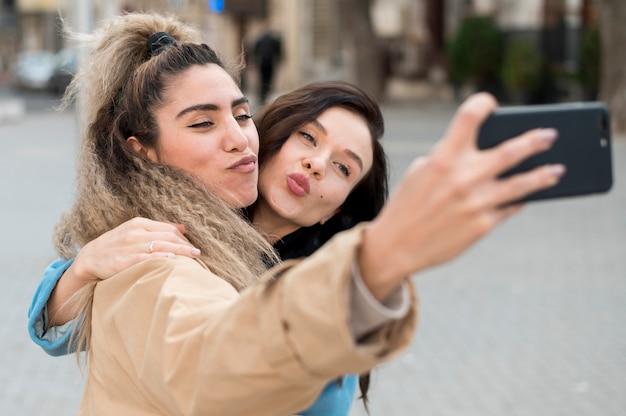 Adolescentes de close-up tomando uma selfie juntos