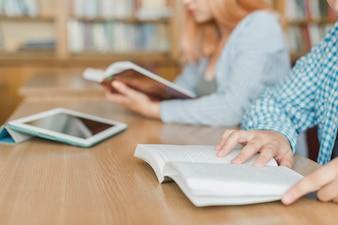 Adolescentes de colheita lendo na biblioteca