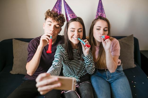 Adolescentes de vista frontal tomando um selfie