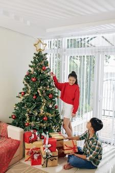 Adolescentes decorando a árvore de natal