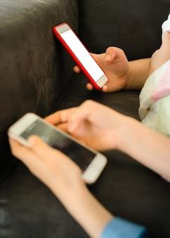 Adolescentes deitadas em um sofá segurando um smartphone com uma tela em branco