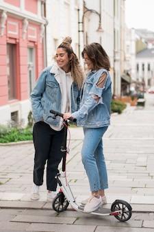 Adolescentes elegantes posando com scooter elétrica