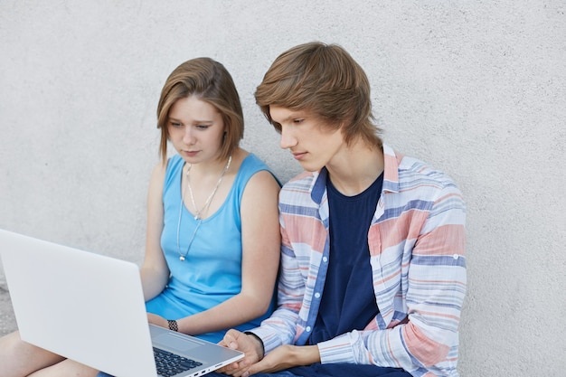 Adolescentes elegantes sentados um ao lado do outro, olhando atentamente na tela do laptop, lendo notícias on-line ou verificando seu feed de notícias