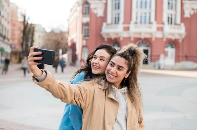 Adolescentes elegantes tomando uma selfie ao ar livre