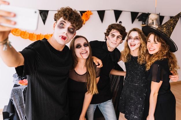 Adolescentes, em, dia das bruxas, trajes, fazendo, selfie