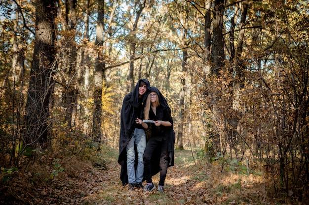 Adolescentes em fantasias de halloween na floresta.
