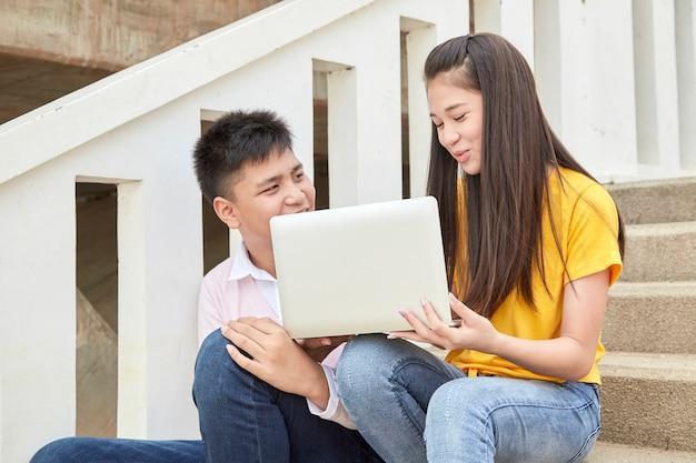 Adolescentes estudantes trabalham trabalho escolar no laptop