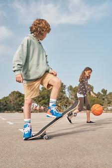 Adolescentes focados no skate e se exercitando com bola de basquete juntos