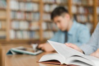 Adolescentes irreconhecíveis, estudando na biblioteca
