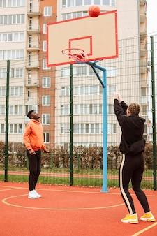 Adolescentes jogando basquete ao ar livre