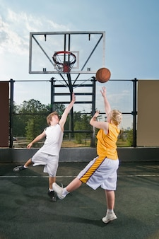 Adolescentes jogando bola de rua