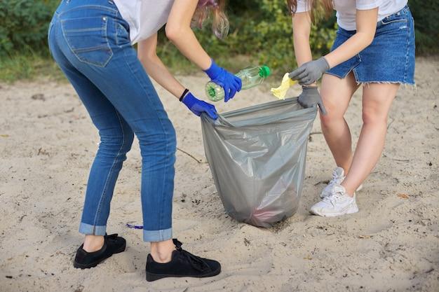 Adolescentes limpando lixo plástico na natureza, margem do rio