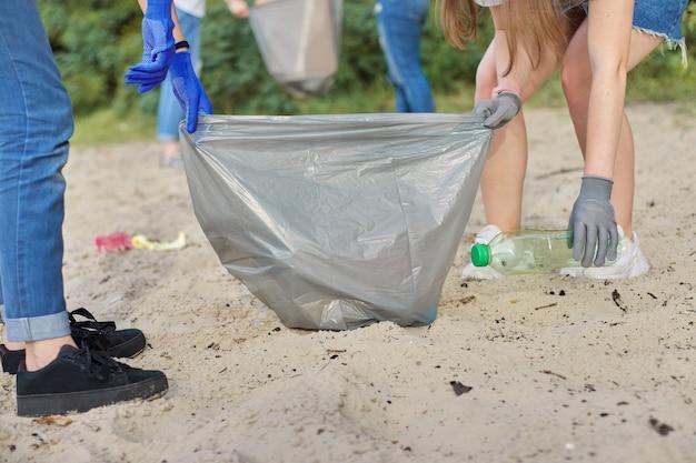 Adolescentes limpando lixo plástico na natureza, na margem do rio. meninas em luvas com sacos de lixo.