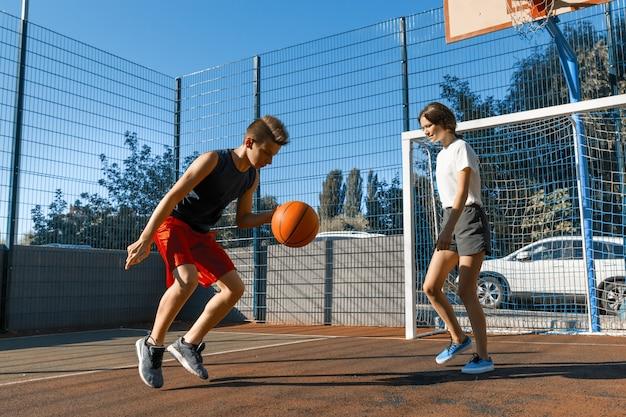 Adolescentes menina e menino com bola, quadra de basquete da cidade ao ar livre
