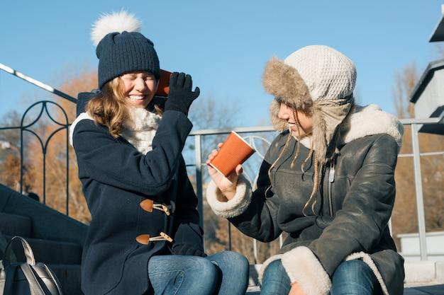 Adolescentes meninas gritam em um copo de papel megafone