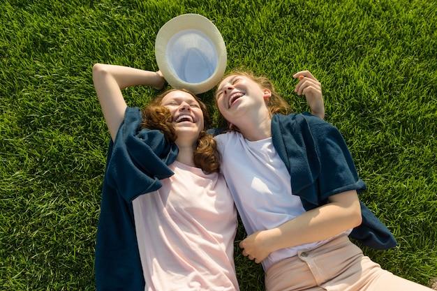 Adolescentes meninas se divertindo, deitar na grama verde