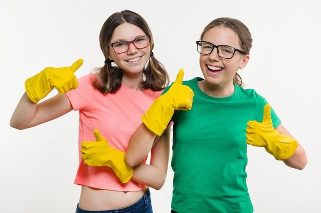 Adolescentes meninas vestindo luvas de proteção amarelas aparecem polegares.
