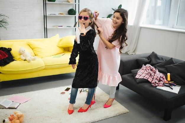 Adolescentes meninas vestindo roupas para mulheres adultas. eles ficam na sala e posando. morena escova o cabelo da amiga. eles se divertem.