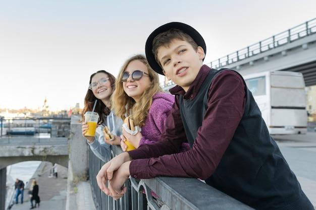 Adolescentes menino e duas meninas com comida de rua falando ao ar livre