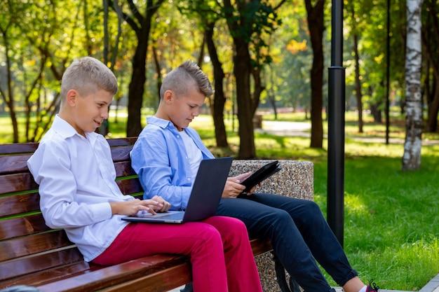 Adolescentes no banco do parque usando laptop e tablet digital