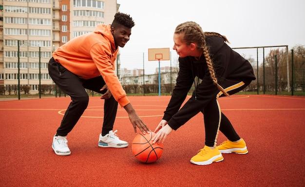 Adolescentes no campo de basquete juntos