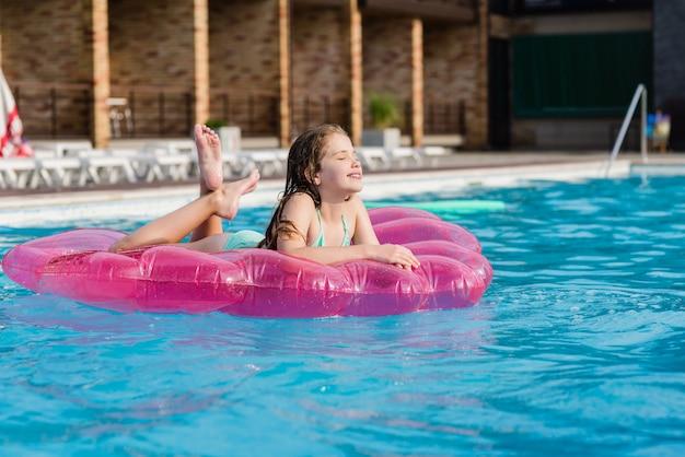 Adolescentes no colchão de ar na piscina