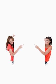 Adolescentes olhando para a câmera enquanto apontam os dedos para um cartaz em branco