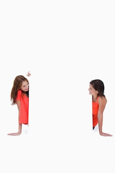 Adolescentes olhando um para o outro na frente de um cartaz em branco