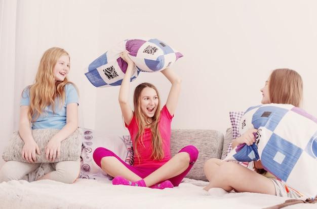 Adolescentes se divertindo e lutando com almofadas