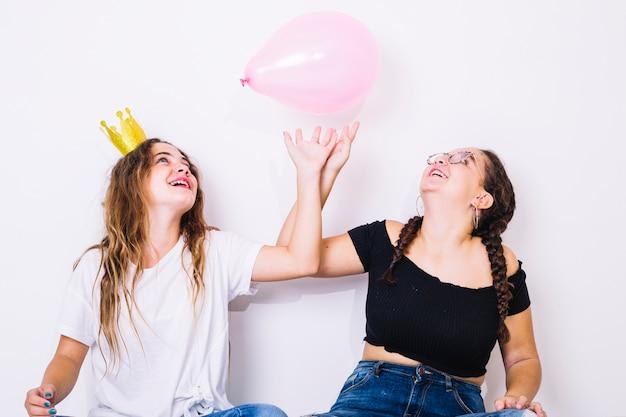 Adolescentes sentados brincando com balões
