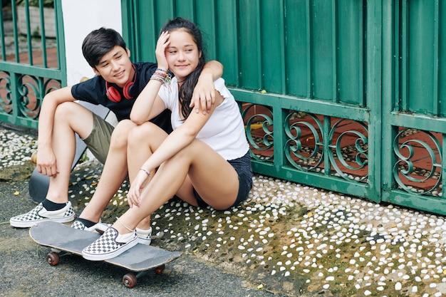 Adolescentes sorridentes sentados ao ar livre