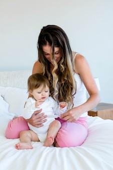 Adorablee bebê sentado no colo da mulher brincando com pente
