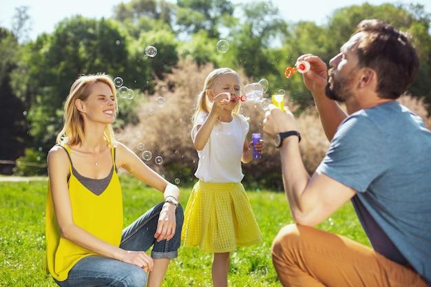 Adoramos bolhas. pais atenciosos e contentes, sorrindo e soprando bolhas de sabão com sua filha