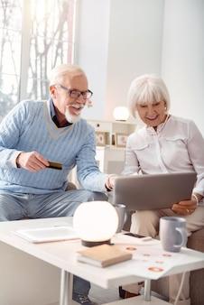 Adoramos fazer compras. idoso otimista e sua esposa escolhendo um item na loja online, apontando para ele na tela do laptop, enquanto o homem entregando seu cartão do banco para fazer um pagamento