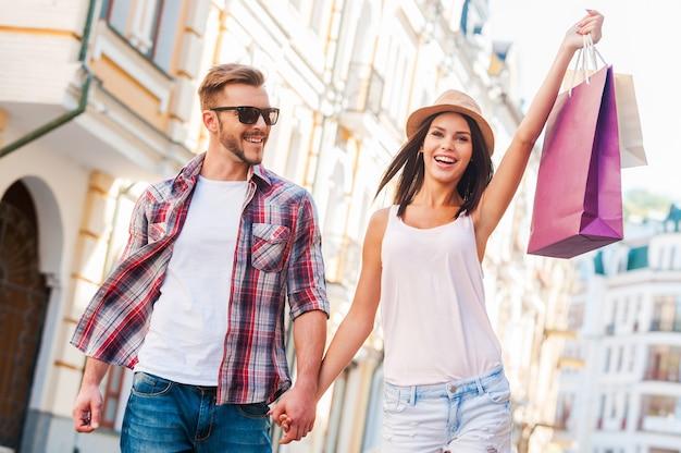 Adoramos fazer compras juntos! jovem casal apaixonado caminhando pela rua enquanto uma linda mulher carrega sacolas de compras e sorri