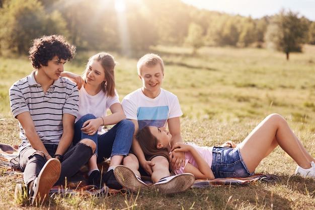 Adoráveis adolescentes apaixonados expressam sentimentos mútuos, têm expressões positivas, fazem piqueniques ao ar livre, sentam-se na manta, gostam de sol e grama verde