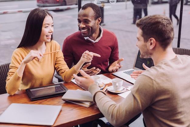 Adoráveis ambiciosos três colegas discutem enquanto gesticulam e riem